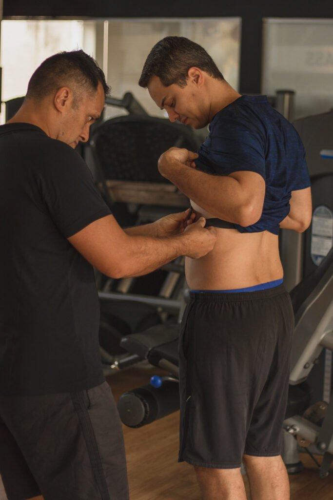 Fitness coach auxiliando aluno durante treino em academia em São José do Rio Preto